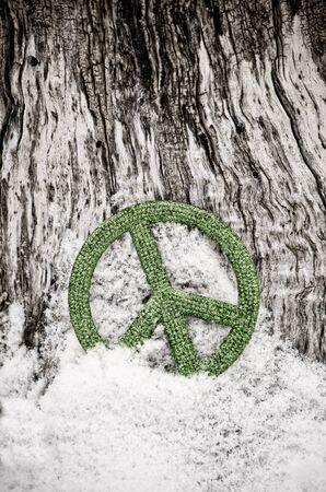 green peace sign ornament in snow against tree Archivio Fotografico