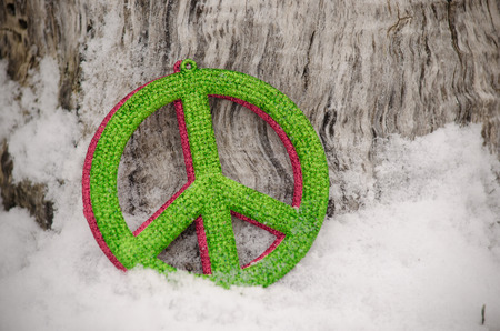 gren and red peace sign in snow against tree