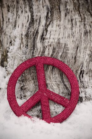 red peace sign ornament leaning against tree in snow