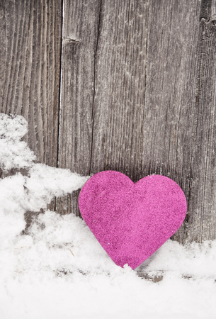 pink heart leaning against rustic fence4