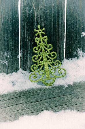 christmas tree leaning against fence in snowvignette