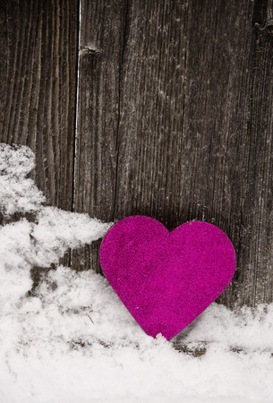 pink heart leaning against rustic fence3