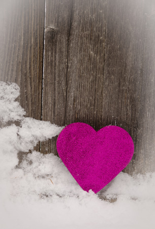 pink heart leaning against rustic fencevignette