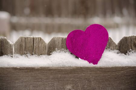 pink heart leaning against rustic fence