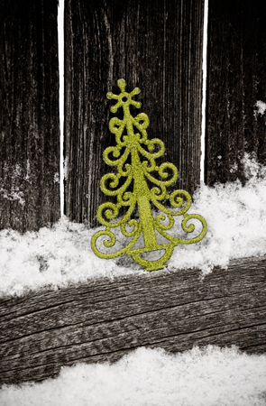 green christmas tree ornament against rustic fence