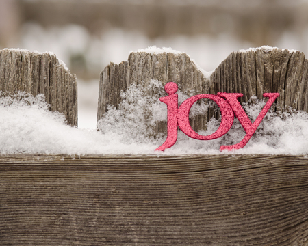 red letters spell joy on snowy rustic fence Archivio Fotografico
