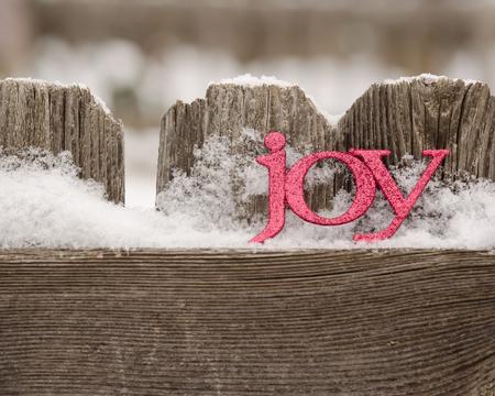 red letters spell joy on snowy rustic fence Reklamní fotografie
