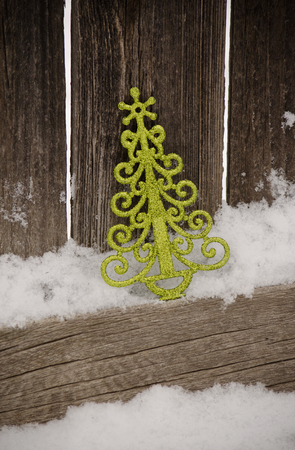 green Christmas tree ornament leaning against rustic fence in snow