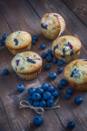 multiple blueberry muffins on wood table