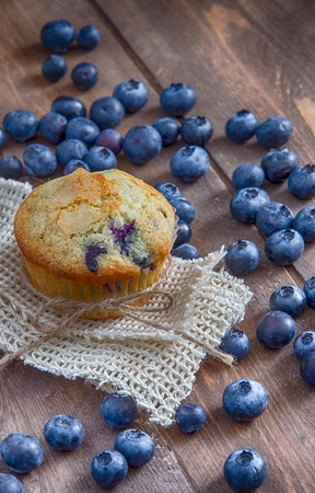 Single bluebery muffin on wood table
