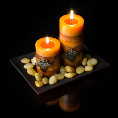 Two orange candles on black background with plate