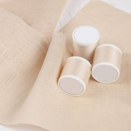 Beige fabric with spool of sewing thread closeup