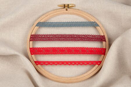 Set of red sewing ribbons on hoop over beige background.