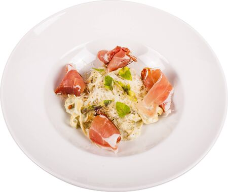 Handmade tagliatelle pasta with pesto sauce and Italian parma, accompanied by cream of parmesan, pine nuts and fresh basil isolated on white Фото со стока - 134118465