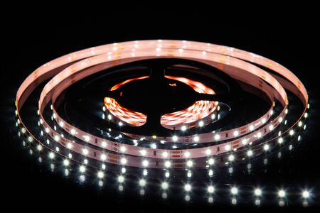 Cold white LED strip on reel with black background Stock Photo