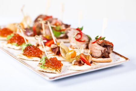 Mini snacks tapas with caviar and meat on white plate