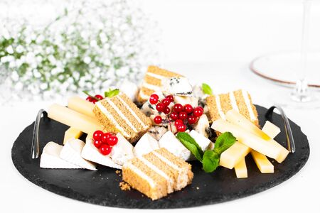 Black cheese plate with red berries and cake isolated on white table