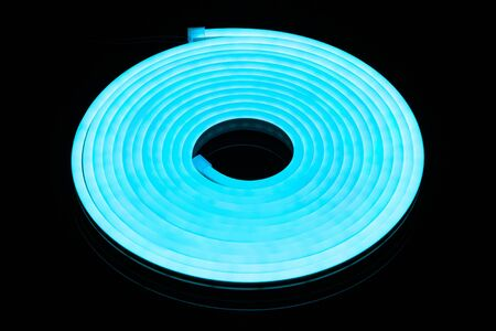 Flexible blue led tape neon flex in roll on black background Stock Photo