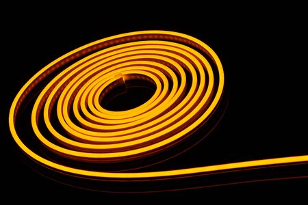 Flexible yellow led tape neon flex in roll on black background Stock Photo