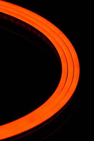 Flexible orange led tape neon flex closeup on black background