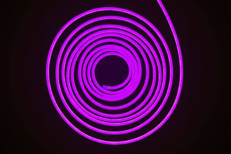 Flexible purple led tape neon flex in roll on black background Stock Photo