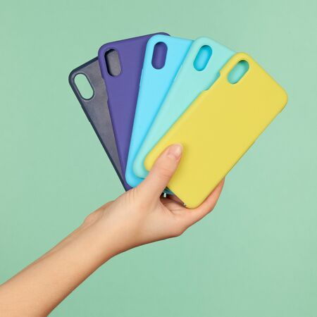 Hand holds the colored covers cases for the phone black, blue, yellow on the green background.