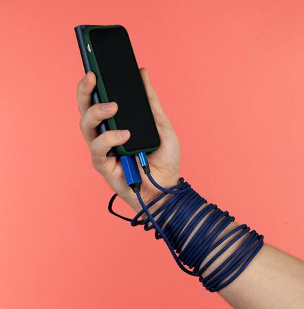 Hand holds phone with powerbank charging blue cable on pink background.