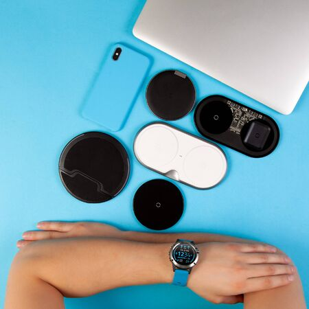 Wireless chargers and blue mobile phone with laptop and hands on desl top view.