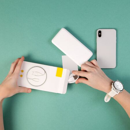 Famale hands open white box with charging cable and white mobile phone with powerbank on green desk top view unboxing.