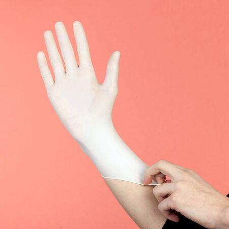 Hands of person putting on a medical glove isolated on pink.