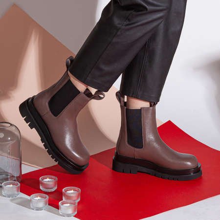 Women's legs in black pants and brown short shoes on medium heel stands in the studio against a colored background. 免版税图像