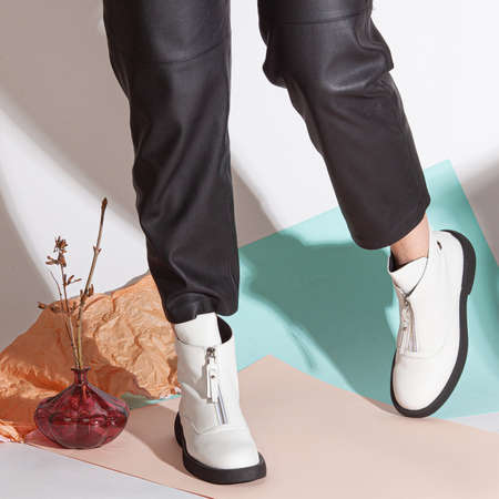 Women's legs in black pants and white short shoes on medium heel stands in the studio against a colored background.