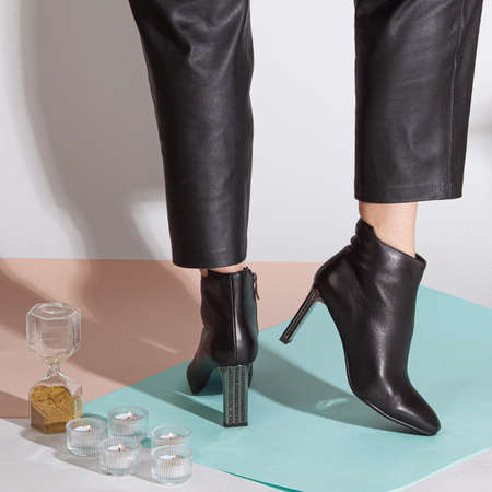 Women's legs in black pants and black short shoes on medium heel stands in the studio against a colored background. 免版税图像