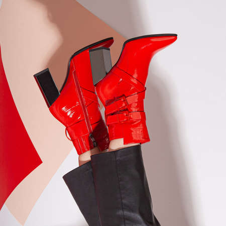 Women's legs in black pants and red short shoes on medium heel stands in the studio against a colored background.