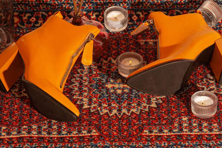 A set of women's shoes shot in the studio against the background of the carpet in retro style with candles.