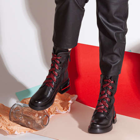 Girl legs in black pants and boots standing on colorfull background in studio.