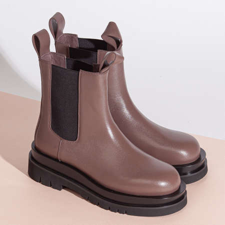 Pair of new brown women short boots on medium high heels on beige background studio shot.