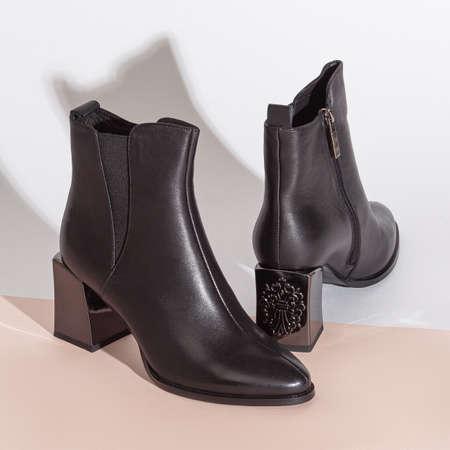 Pair of new black women short boots on medium high heels on beige background studio shot.