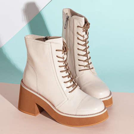 Pair of new white women short boots on medium high heels on beige background studio shot.
