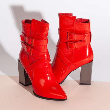 Pair of new red women short boots on medium high heels on beige background studio shot. 免版税图像