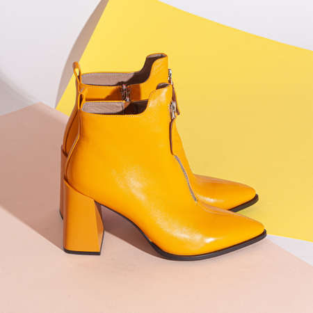 Pair of new brown orange women short boots on medium high heels on beige background studio shot.