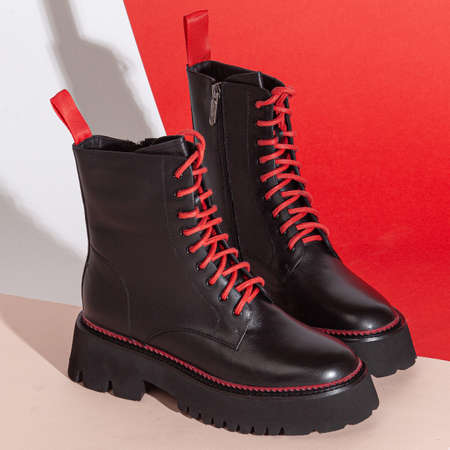 Woman's big balck shoes boots with red laces in studio.