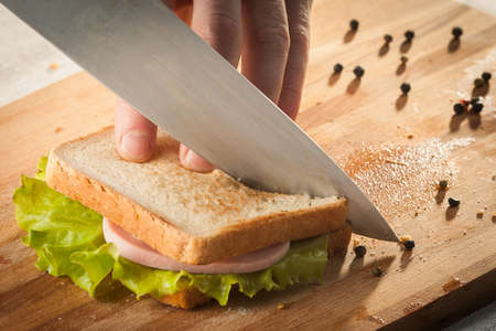 Cutting sandwich with bread, cheese, salad and ham with hands on wooden cutting board with knife. Foto de archivo