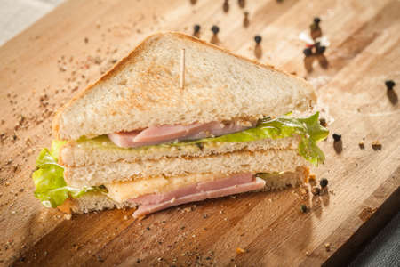 Cut by half sandwich with cheese, salad and ham. Foto de archivo