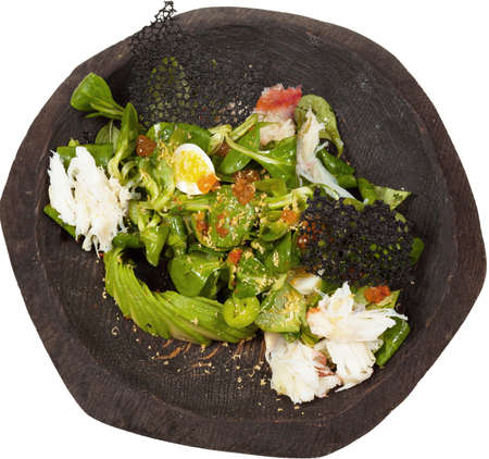 Salad with red caviar and crab in black wooden bowl isolated on whaite background.