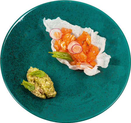 Tuna Tartar with guacamole sauce and crackers on green plate isolated.