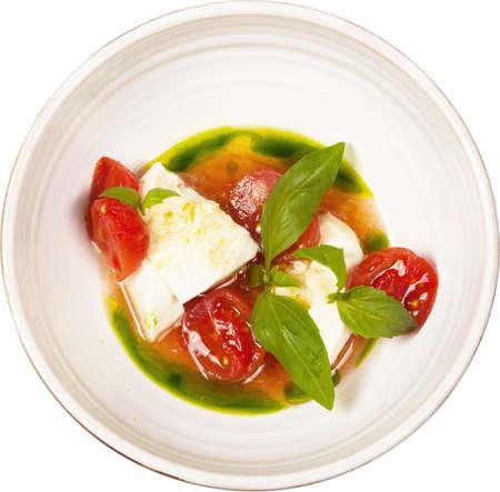 Caprese salad on round bowl isolated on white background. Foto de archivo