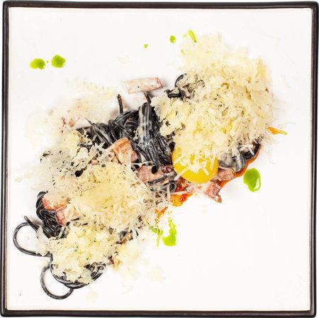 Black spaghetti with farm piglet brisket, sun-dried tomato pesto and yolk sauce on white square plate. Foto de archivo