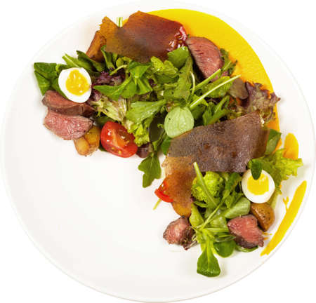 Salad with roast beef, baked potatoes, cherry tomatoes and root mousse isolated on white background. Foto de archivo