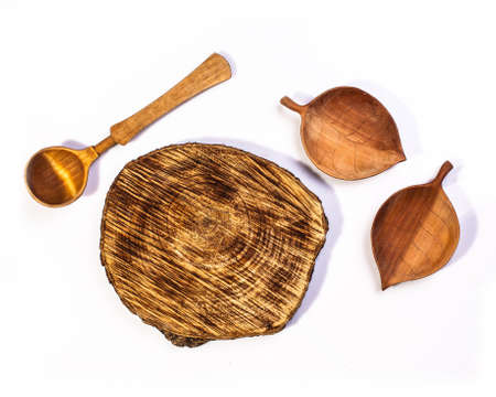 Set of kitchenware accessory - Wooden plate, wooden spoons and wooden small bowls on white background. Foto de archivo